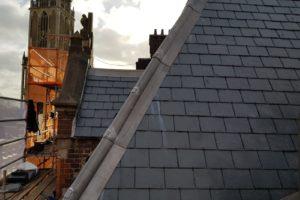 Authentieke waterafvoer belegd met wapenschilden op hersteld dak Choorstraat Utrecht nmet uitzicht op Domtoren