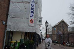 Ingepakte steiger op de hoek van gevel Springhavertheater in Utrecht. Schilder poseert onder logo Joh. van Doorn De Bilt BV.